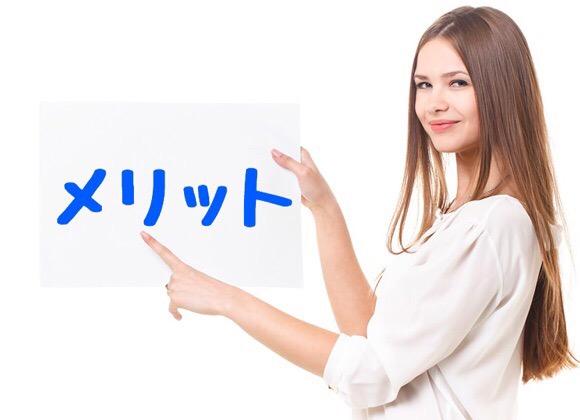 『メリット』と書かれたボードを持つ女性