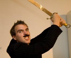 剣を振り下ろそうとする髭の男性