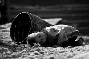 大きなカゴの横で横たわる子供