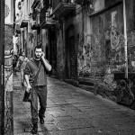壁に悪魔の顔が落書きされた街を歩く男性のモノクロ写真