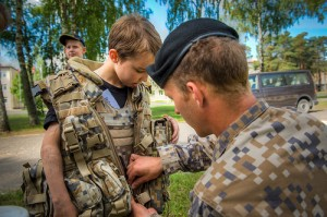 迷彩のジャケットを子供に着せようとする軍服の男性