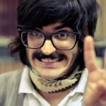 黒縁メガネの黒髪、ヒゲのの男性が満面の笑みでピースサイン