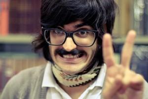 黒縁メガネの黒髪、ヒゲの男性が満面の笑みでピースサイン
