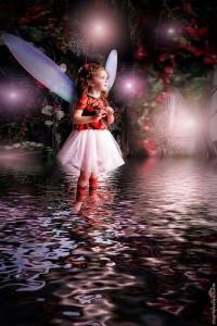 妖精のような羽根を付けた女の子が水面に浮かぶ