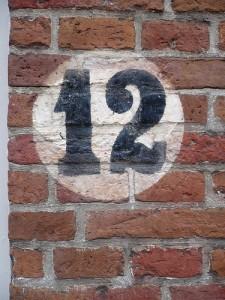レンガの壁に白い丸の中に黒字で12と書かれている