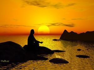 沈み行く夕日をバックに浜辺で座禅を組む人