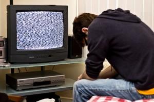 映らないテレビにうなだれる男性