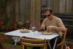 テーブルでナイフとフォークで食事するサングラスの男性