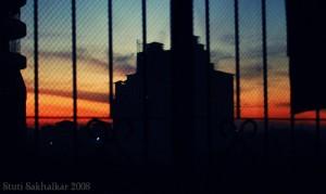 夕日が沈む空とビルを窓越しに見る