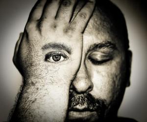 右目を手で覆う男性。その手には目が