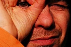 右目の前でオーケーの合図をする男性の顔のアップ