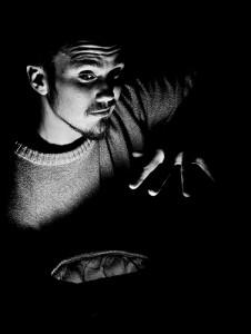 暗闇の中でマジシャン風の男性が左手をかざす
