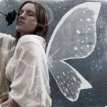 黒いバラを持ち、白い服を着た女性。背中には白い羽と鱗粉が見える