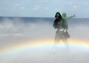緑のレインコート。霧が立ち込め虹が足元に
