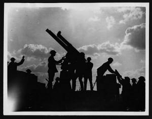 大砲に玉を入れる兵士達のモノクロ写真