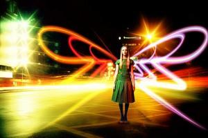 道路に立つ少女の背中にネオンの光が蝶の羽のように