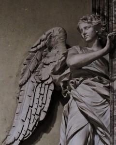 翼の生えた女性の姿で衣を羽織る天使風の石像