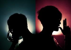 赤と青の背景に影だけ映る2人の男性
