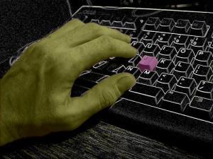 キーボードを押す左手と一つだけ赤いキーボード