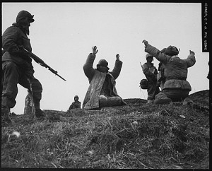 丘の上で銃を構える兵士と手を挙げる兵士