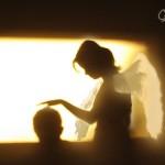 子供の頭に手をかざす天使の影