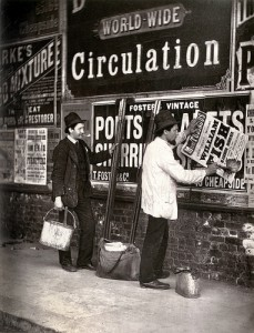 看板の上から広告を貼る2人の男性の白黒写真