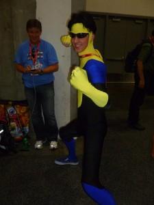 蛍光の黄色と青のタイツを着てポーズをとるサングラスの男性
