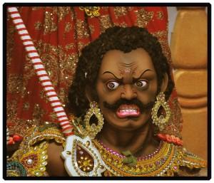 頭パンチパーマで髭を生やし、ピヤスと金の装飾品で飾る、すごい形相のインドの神様風の男性
