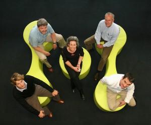 4人の老若男女が黄緑の椅子に座り上を見ている