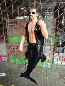 グラサンをかけ、裸に黒の袖なしジャケットを着る男性の人魚の人形