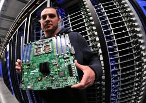 スーパーコンピューターの前で基盤を持つ男性