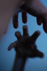 何かを掴み取ろうとする手が鏡に映る