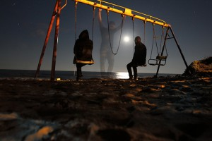 夜の公園のブランコに乗る男性と女性の間に立つ幽霊のように透明な男性