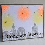 congratulationsと書かれた色紙に街並みと花火