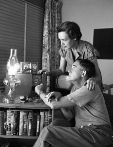 ラジオを椅子に座って聞く男性とそれに寄り添う女性